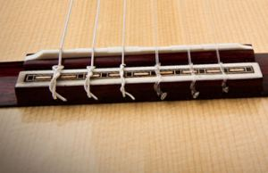 Классическое крепление струн на подставке гитары