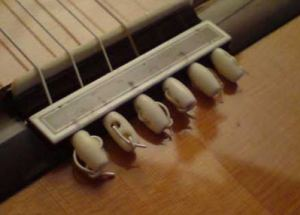Крепление струн на подставке гитары с помощью бусинок